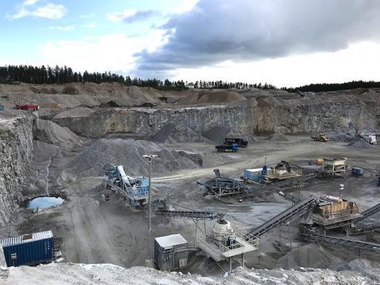 Finkornig granit som bryts i Malmby bergtäkt. Inom Malmbytäkten har man visat att denna bergart kan förädlas till flera olika ersättningsmaterial för naturgrus. Det mesta av bergmaterialet från denna täkt levereras till betongtillverkning.