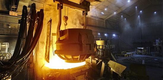 Chargering (insättning) av stålskrot vid Ovakos ljusbågsugn i Hofors.Skrotkorgen som är på väg att öppna innehåller 70 ton skrot.